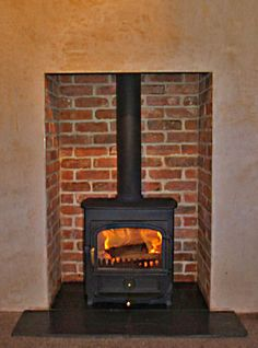Reclaimed brick slip chamber with slate tiled hearth and Clearview Vision 500 multifuel stove. Fitted in Danbury, Essex 2007