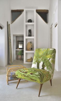 Clous de la pièce, une chauffeuse Tabarka en tissu vintage tropical, un porterevues en rotin et une colonne architecturée qui collectionne des poteries de Sejnan.