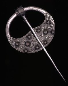 9-10th C. Ireland. Silver bossed penannular brooch; saltires + 5 collared bosses on each terminal; interlaced animals and billeted pattern; circles + triquetra...