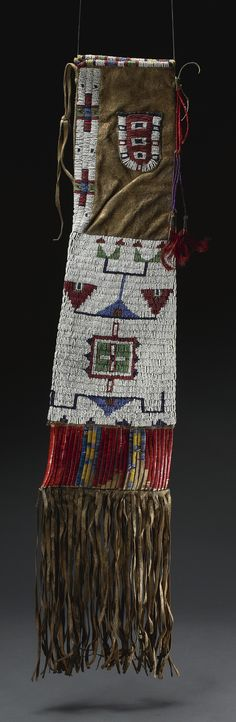 SIOUX BEADED AND FRINGED HIDE PIPE BAG sinew sewn in opaque beadwork with metal bead accents, with typical geometric designs on each side, the lower cut hide section wrapped in dyed-quillwork; decorated with a small beaded pouch beneath the opening. length without fringe 25 in.
