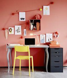 Um espaço de trabalho muito criativo, de cores vivas, decorado com ilustrações penduradas por cima da secretária