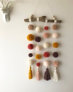 Whimsical pom pom hanging featuring partially wool wrapped driftwood, natural wooden beads, 20 handmade pom poms of various sizes, and 4 large...