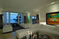 Crisp, clean white furniture combines with neutral walls and floor-to-ceiling windows for a bright, breezy atmosphere in this living room. Contemporary paintings add vibrant color, and a waterfront view provides a stunning backdrop.