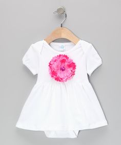 The perfect blend of fun and fancy, this piece looks like a dress but is actually a skirted bodysuit with a lap neck and snaps at the bottom, so staying comfy and changing diapers couldn't be easier. A dazzling flower in front shows off budding style at its finest.100% cotton exclusive of decorationMachine wash; tumble dry