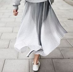 The beautiful movements of a pleated maxi skirt as the wind gently blows.