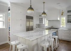 White shaker cabinets framed with white herringbone cooktop tiles shine bright in this transitional kitchen design. Transitional Lighting, Transitional Bathroom, Transitional Decor, Magnolia Kitchen, White Shaker Cabinets, White Marble, Marble Top, Marble Countertops, Kitchen Design