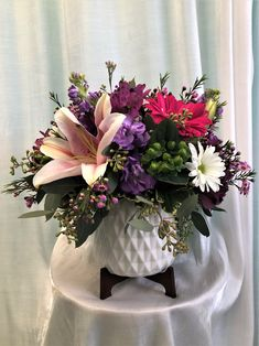 Lilies, gerbera daisies, stock and more in an on trend porcelain pedestal container.