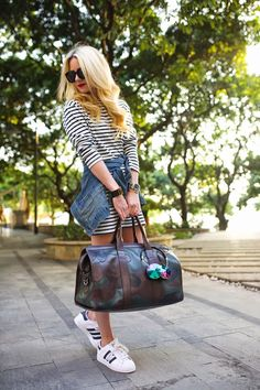 striped dress with denim jacket and duffel bag
