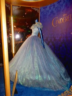 "In this view of Cinderella movie ball gown you can see more of the lighting. According to Jason of Hollywood Movie Costumes and Prop ""Cinderella's ball gown is adorned with butterfly details, as our heroine has a special affinity with nature and animals, and has over 111,000 light-refracting Crystal Blue Aurora Borealis and Clear crystals. The show-stopping ball gown is made up of 24 layers of tulle and has a circumference of 11.6 metres.  In person the blue of the dress is not as strong as…"
