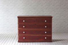 A 19th Century red painted pine chest of drawers.   Four long drawers with white porcelain knobs. We did quite a lot of loving repair work on this unusual piece which has turned out beautifully....