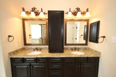 Kinsmen Homes Katherine plan bathroom with rich dark brown cabinets, granite countertops, double vanities and oil rubbed bronzed fixtures.