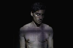 Young man Covered by Abstract Patterns of Light / Gem Fletcher