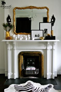 gold mirror, fireplace, mantel, white candles, framed photographs, black white and gold fireplace fancy  VIA