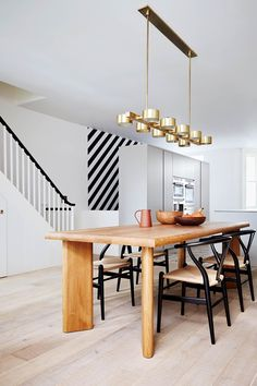 A custommade brass pendant light hangs above an oak dining table paired with a set of 'Wishbone' chairs by Hans J Wegner