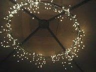 1 hula hoop (spray painted)   2 icicle strings of lights and black electrical tape = chandelier. Done.
