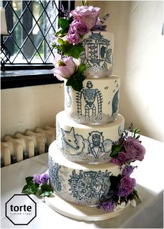 STUDIO GHIBLI Handpainted wedding cake featuring scenes from the couple's favourite Studio Ghibli films, with trailing fresh flowers #wedding #cake #lancashirewedding #paintedcake #studioghibli #freshflowers