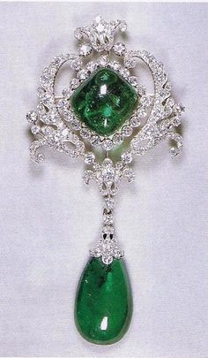 The Campridge and Delhi Durbar Parure - This diamond scroll with a central lozenge-shaped emerald was made by taking the main portion from the centre of Queen Mary's stomacher and hanging the emerald drop from Cullinan VIII from it.