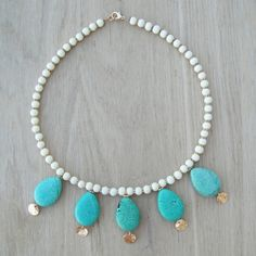 Coucou Suzette Necklace This is a tribal inspired handcrafted statement necklace. The materials are white glass beads, turquoise magnesite and gold brass hook, spacer