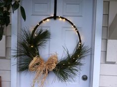 Pine boughs, rusted wine barrel ring, raffia and lights. All things I had around the house!