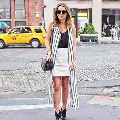 A long striped vest, cami, fitted skirt, and ankle boots.