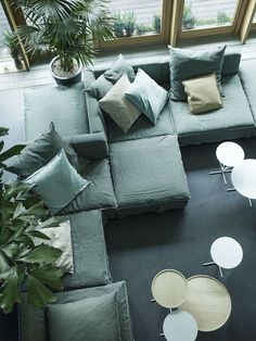 Grey modular sofa by Paola Navone. Loving the angular lines of the sofa and the cluster of circular tables: