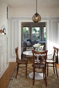 A small dining room that really works. I love the ceiling lamp, the chairs and the white tulip table