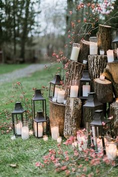 Ceremony backdrop made of tree trunks decorated with lanterns and candles - Woodland Romance Wedding Inspiration by Emily Wren Photography - via ruffled