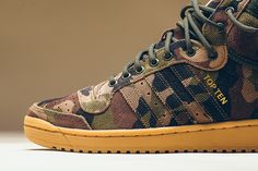 """The adidas Top Ten Hi returns in a new """"Camo"""" colorway featuring a durable canvas upper and gum outsole with gold branding. Available today for $90 USD."""