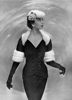 1955 Marie-Hélène in black wool cocktail suit trimmed in white mink by Jacques Fath, hat is white mink with pink rose,