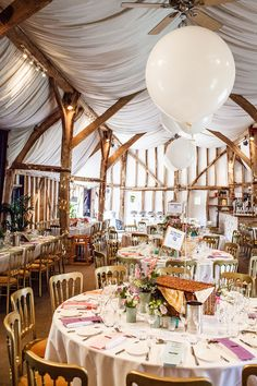 Rustic barn wedding reception - Image by Lina and Tom Photography - An outdoor DIY wedding ceremony in Cambridgeshire England with bright blue colour scheme, huge balloons, many rustic home made touches, dress by Allure Bridals