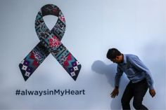 A Malaysia Airlines (MAS) staff does a final check on the #alwaysinMyheart billboard outside the Malaysia Airlines Academy in Petaling Jaya, 08 March 2015. - EPA pix