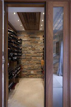 Ambiente para adega climatizada, com vinhos em painel de madeira, parede com tijolinho