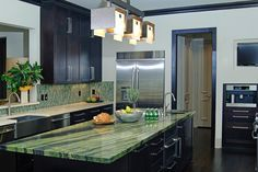 This chic, high-contrast kitchen gets a shot of energy from its gorgeous green island countertop and tile backsplash.
