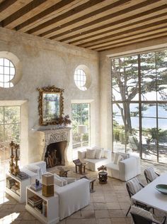 """In the ethereal living room, 20-feet high steel framed windows and doors frame the ocean view. Walls were hand-plastered to suggest antiquity.Time Travel: A Brilliant Design Invention. North of Malibu on a bluff overlooking Broad Beach, Richard Shapiro created a romantic villa with a splash of Mediterranean style. """"I wanted everything to look old, worn, faded, weathered, and rough,"""" he said. Faded frescoes by Ilia Anossov add to the look of the Renaissance."""