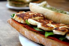grilled halloumi sandwich                                       2 ciabatta loaves, 10 thin slices chorizo,   Block of halloumi cheese (quickly pan fried or grilled),  Baby Spinach, Green pesto
