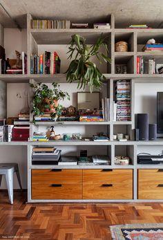 Sala de estar tem estante de concreto aparente com nichos de diferentes tamanhos.