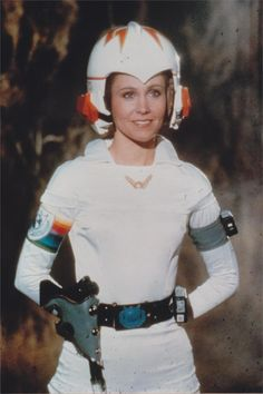 Erin.  Good example of two piece that looks like a suit.  70's helmet.  Cute collar.  Armbands and belt with accessories.
