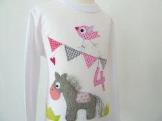 Ein aufwändig gestaltetes Kindersshirt mit Eurem Wunschzahl in Weiß aus 100% Bio-Baumwolle.  Gerne kann das T-Shirt auch in andere Farbkombinat...