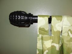 Cheap, simple, easy extra touch to add to the military Army theme in our boys bedroom. I found clear plastic grenades filled with water balloons at the $1 store. I emptied out the balloons and spray painted them black. Then drilled a hole in the lid the size of the curtain rod. I added them to both ends of the curtain rod.