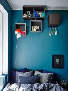 Coloque caixas para arrumação na parede bem alto na parede, para criar arrumação que não atrapalha e espaço para exibir objetos.