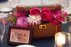 Instead of using vases to hold flowers, to continue with our travel theme, we used vintage suitcases. It took MONTHS to find these suitcases, but we went to several antique shops , goodwill, and of course craigslist to find enough for each table. Since the reception was at the Pennsylvanian (an old train station) we labeled each (ikea) frame as a 'Track' number. That map background was a photo copy of a vintage map I googled and printed.