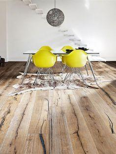 Lindo piso de madeira e mesa com cadeiras amarelas.