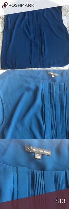 Blue sleeveless shirt Beautiful blue color, on the teal-blue side. Sleeveless, although the shoulders are wide so might fit much re like a cap sleeve depending how wide your shoulders are. Has a couple minor pulls in the back, which can be adult be hidden under jacket or sweater. Tops