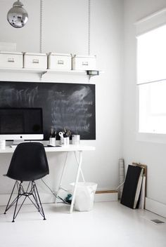 White home office with blackboard wall.