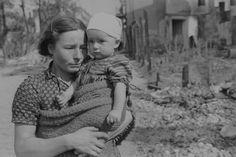 A woman with a child in the ruined streets of Warsaw.