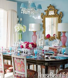 In the dining room, walls in Farrow & Ball's Blue Ground in Full Gloss are a foil for pink Murano glass lamps from Swank Lighting. Vintage Louis XVI–style chairs around a Jansen dining table are covered in Talcy Velvet by Clarence House.   - HouseBeautiful.com