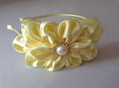 Tiara de metal revestida com fita e acabamento nas pontas para não machucar, super leve e confortável, com linda flor em casquete amarela pérola e strass.
