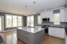 Gray kitchen island. White kitchen cabinets. Red sink faucet. Contemporary pendant lights.