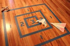 PAPER PLANE AIRPLANE TARGET! This looks like some great indoor play! Perfect for a rainy day!! (I'd use painters tape if putting it on a floor so there isn't any of that sticky residue left).