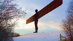 A steel sculpture of an angel with wings. It stands on snow covered ground. ( Anthony Gormley's Angel of the North)